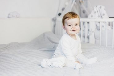 Cute baby boy on bed - Top 100 baby names in Iceland