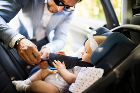 Dad putting baby in a rear-facing car seat