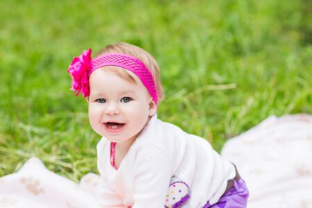 Baby with pink bow on the grass - Swedish girl names