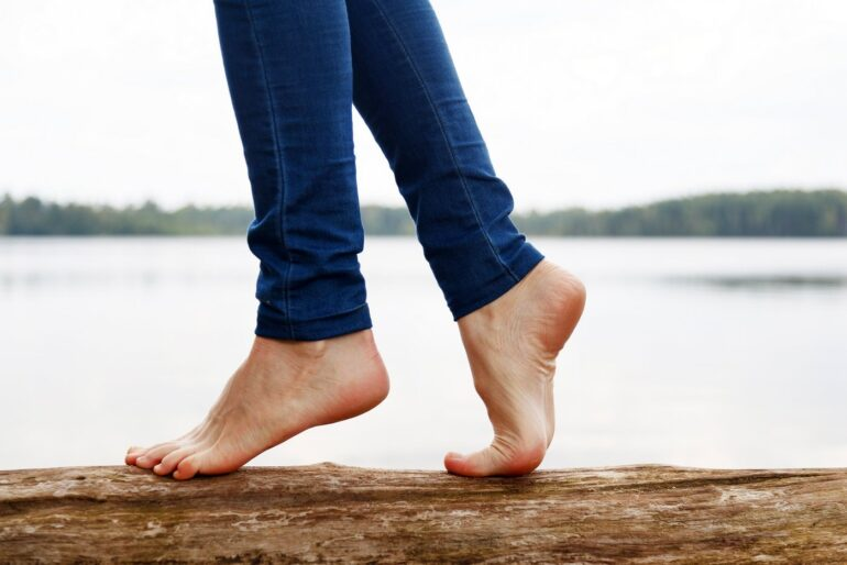 Woman barefoot walking on a log